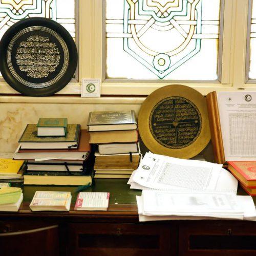 Una mesa y muchos libros contra el muro de orientación a La Meca, o quibla